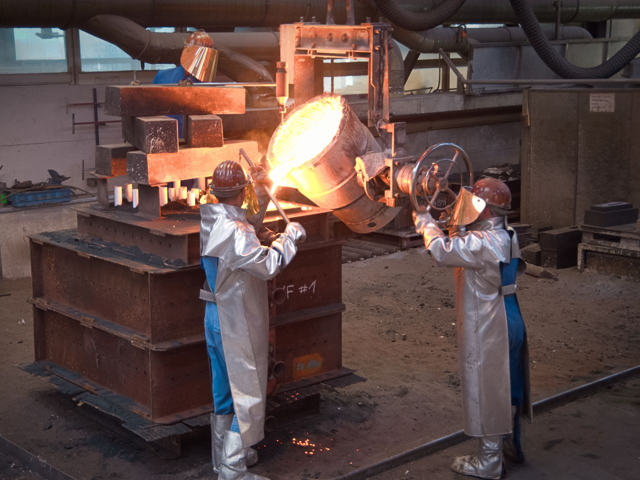 Foundry worker casting steel on particularly large sand mold