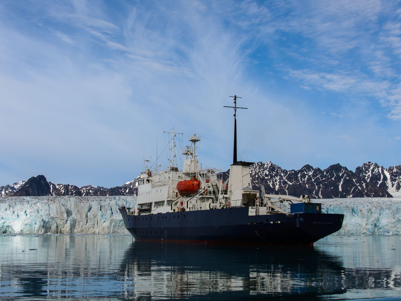 Icebreaker on the water in front of ice and mountain landscape
